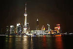The Oriental Pearl TV Tower on the Huangpu River in Shanghai, China at night from the Bund riverwalk .