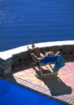 Vacationer sunbathes on a deck overlooking the Agean Seaon the Greek Island of  Santorini