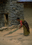 A Nepalese woman sweeps in front of her home in the village of Thakali