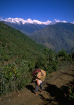 Porters moving along trail near the village of Syabru with a view of the Langtang rue in the background.