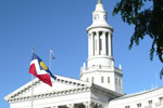 The bell tower and city flag of Denver Colorado's city and county building can be seen from Civic Center Park in downtown Denver.