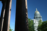 The Colorado State capitol in downtown Denver,Colorado is framed by the pillars of a nearby building.