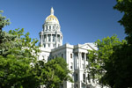 The Colorado State capitol in downtown Denver,Colorado is framed by trees on the capitol grounds.