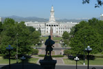 Denver Colorado's City and County building is seen in the distance from a statue of a civil war soldier is silouhetted on the state capitol grounds.