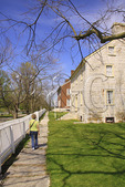 Tourist strolls by historic buildings at Shaker Village of Pleasant Hill, Harrodsburg, Kentucky