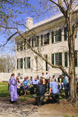 Costumed interpreter talks to tourists in front of Centre Family Dwelling at Shaker Village of Pleasant Hill, Harrodsburg, Kentucky