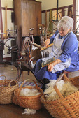 Costumed interpreter spins yarn at East Family Sisters Shop at Shaker Village of Pleasant Hill, Harrodsburg, Kentucky