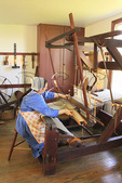 Costumed Interpreter demonstrates weaving in East Family Sisters Shop at Shaker Village of Pleasant Hill, Harrodsburg, Kentucky