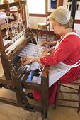Costumed interpreter demonstrates weaving in East Family Sisters Shop at Shaker Village of Pleasant Hill, Harrodsburg, Kentucky