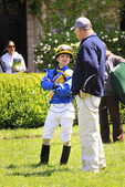 A thoroughbred trainer and jockey talk in the paddock before a race at Keeneland Race Course, Lexington, Kentucky