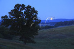 Full moon sets behind Blue Ridge Mountains on farm in Swoope, Shenandoah Valley, Virginia