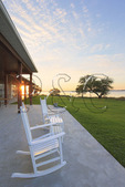 Rocking chairs on patio overlooking sunset over Bogue Sound, Country Club of Crystal Coast, Atlantic Beach, North Carolina, USA