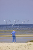 Man stands on beach looking out at Pamlico Sound, Cedar Island, North Carolina, USA