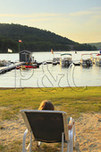 Visitor watches the sun go down on the beach at Silver Tree Marina on Deep Creek Lake, Thayerville, Maryland, USA