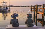 Child statuaries on dock at sunset, Silver Lake Harbor, Ocracoke Island, Cape Hatteras National Seashore, North Carolina, USA