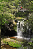 Hikers pause on the bridge over Elakala Falls in Blackwater Falls State Park, Davis, West Virginia, USA
