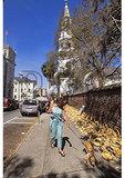 Woman walking dog past sweet grass baskets, Saint Michaels Church, Charleston, South Carolina