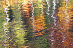 Shimmering sunlight and wafting breezes create abstract autumn reflections on the fiord-like surface of Lake Lure in the mountains of western North Carolina.