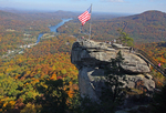 An American flag stands watch over the surface of the granite promontory of Chimney Rock in the recently-christened Chimney Rock State Park.  Until 2006 when it was deeded to the State of North Carolina as state park land, Chimney Rock was privately owned and operated for almost 100 years.  The fiord-like surface of Lake Lure bisects the autumnally-tinged forests in the valley below.