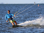Kite surfer zipping along water surface.