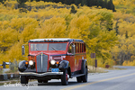 Red Jammer bus crosses the St Mary bridge in autumn in Glacier National Park in Montana