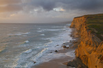 Sea cliffs catch days last light at Pomponi State Beach in San Mateo County, California, USA