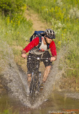 Mountain biker splashes through Andrews Creek on the Maah Daah Hey Trail in Medora, North Dakota, USA model released