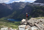 Hiker overlooking Medicine Grizzly Lake on the Triple Divide Pass Trtail in Glacier National Park, Montana, USA model released