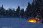 Tent glows at dusk during winter camping near West Glacier, Montana, USA