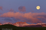 Full moon sets over the Rocky Mountain Front at sunrise near Augusta, Montana, USA