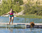 Girl and her dog jump from dock into Foys Lake in Kalispell, Montana, USA
