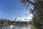 Jumping off a tree rope on a summer day at Champion Lakes Provincial Park, British Columbia, Canada, model released