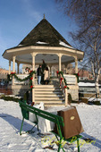 Gazebo decorated for Christmas, gift bags lining the bench