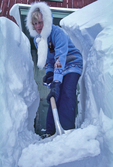 female with arctic fox fur on coat/ shovelling snow