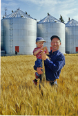 Farmer in spring wheat field with son. Grain bins in the background