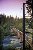 hiker on bridge over the Grass River, Pisew Falls Provincial Park, Manitoba, Canada