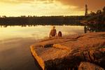 hiker along Canadian Shield rock at sunrise, Namau Lake, Whiteshell Provincial Park,