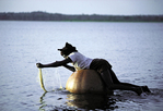 a Gwari man checks his fishing net while floating on a gourd, near Minna, Nigeria