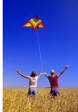 two girls fly a kite in a mature spring wheat field, near Winnipeg, Manitoba, Canada