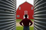 closeup of grain bins with man and red barn in the background near Torquay, Saskatchewan, Canada