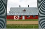 closeup of grain bins with red barn in the background near Torquay, Saskatchewan, Canada