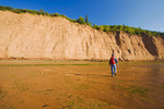 hiker at low tide along sandstone cliffs, Cape Blomidon Provincial Park in the Minas Basin, Bay of Fundy, Nova Scotia
