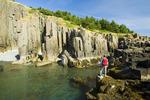 hiker along basalt rock cliffs, Brier Island, Bay of Fundy, Nova Scotia, Canada
