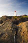 volcanic rock with Boar's Head Lighthouse in the backgrpond, Long Island, Bay of Fundy, Nova Scotia