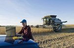 a farmgirl uses a computer during the soybean harvest with a combine harvester in the background, near Lorette, Manitoba, Canada