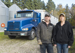 a farmer and his wife stand next to thier farm truck being loaded with grain for transporting to an inland grain terminal,near Dugald, Manitoba, Canada
