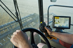 a farmer operates the autoguidance system on his new combine during the soybean harvest, near Dugald, Manitoba, Canada