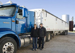 a female farmer and husband  stands next to their farm truck loaded with grain to be transported to an inland grain terminal,near Dugald, Manitoba, Canada