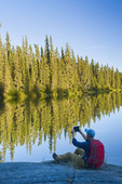 a hiker takes a photo using a tablet, along the Grass River, near Pisew, Manitoba, Canada
