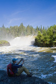 hiker taking a photo at  Pisew Falls along the Grass River, Manitoba, Canada